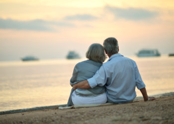 Portrait of happy mature couple relaxing on beach at sunset